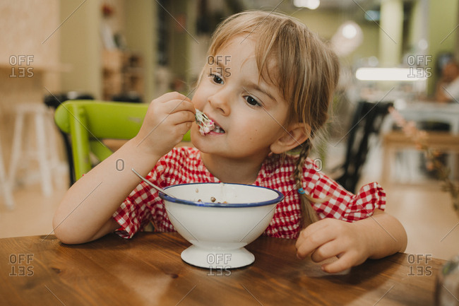 Appetizing fragrant food in white bowl and adorable girl eating with hands at table