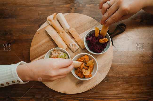 From above crop unrecognizable hands grabbing assorted vegetable dips with crispy crunchy bread in bowl on round stand on table