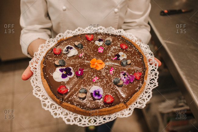 From above tasty appetizing cake festively decorated with bright flowers in hands of woman