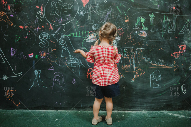 Back view of unrecognizable adorable child drawing at school during class in a writing green board