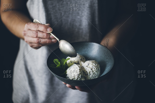 Crop view of anonymous woman with spoon in hand and holding bowl with stracciatella ice cream balls decorated with mint leaves