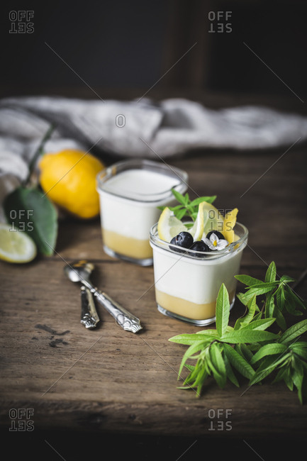 From above view of still life of glass with homemade yoghurt and lemon curd decorated with blueberries and flowers placed on wooden surface