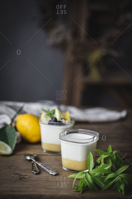 Still life of a couple of glasses with homemade yoghurt and lemon curd placed on wooden surface