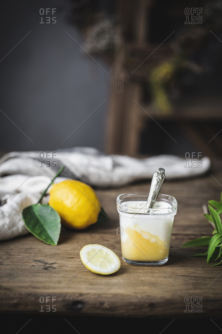 Still life of glass with homemade yoghurt and lemon curd placed on wooden surface with a spoon inside