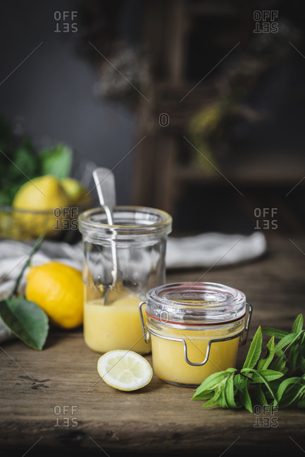 Still life of a couple of glass jars containing homemade lemon curd placed on wooden surface