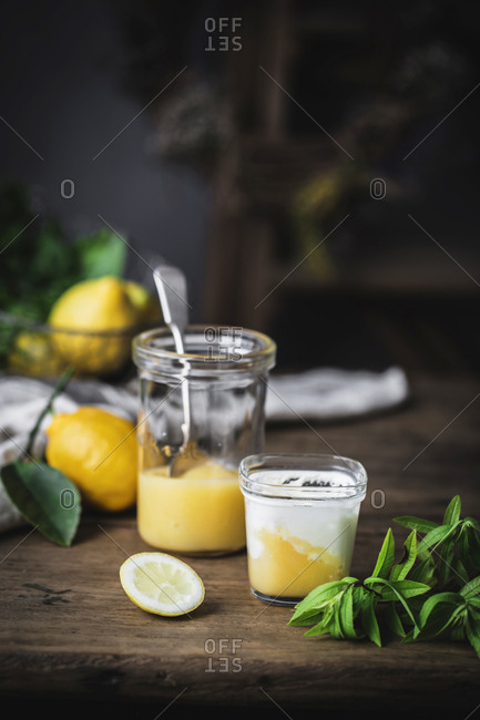 Still life of glass with homemade yoghurt and lemon curd placed on wooden surface