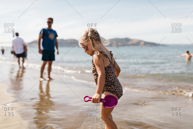 Little girl with shovel playing at East Beach in San Francisco, California