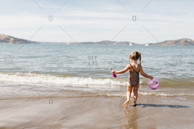 Little girl with shovel and bucket playing at East Beach in San Francisco, California