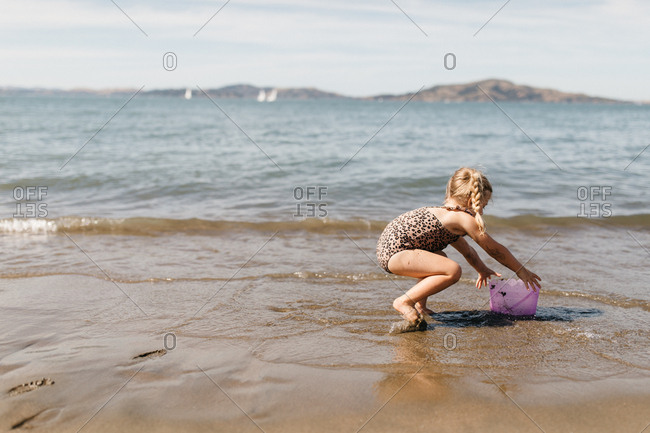 Little girl with bucket playing at East Beach in San Francisco, California