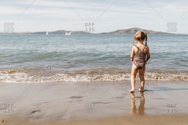 Little girl watching ocean waves at East Beach in San Francisco, California