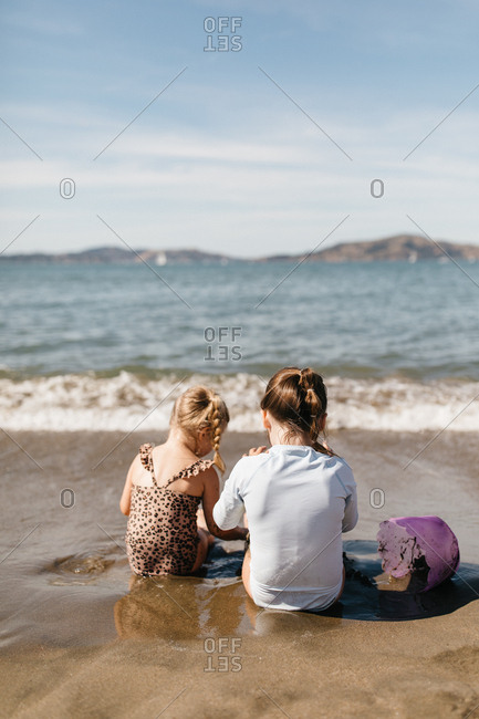 Two girls playing in sand at East Beach in San Francisco, California