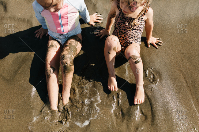 Little girls digging feet into wet sand at East Beach in San Francisco, California