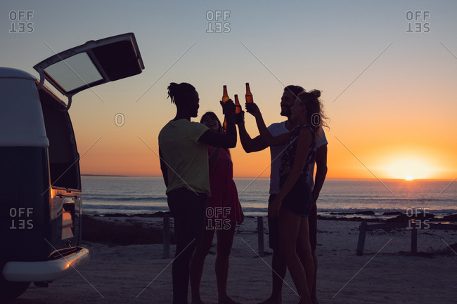 Side view of group of diverse friends toasting beer bottles near camper van during sunset