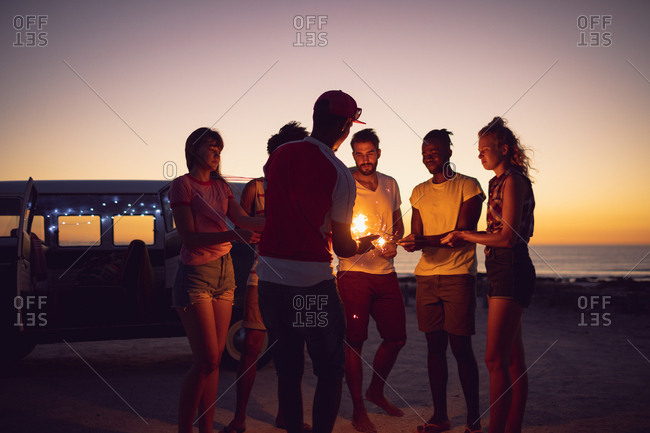 Front view of group of diverse friends lighting sparklers near cameraman during sunset