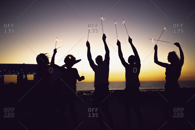 Front view of silhouette of diverse friends playing with sparklers on the beach at dusk