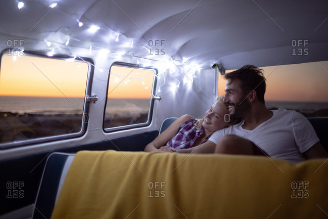 Front view of happy Caucasian couple sitting together in a camper van at beach during sunset