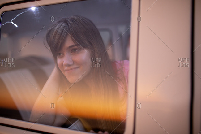 Front view of beautiful Caucasian woman looking through window of a camper van at beach