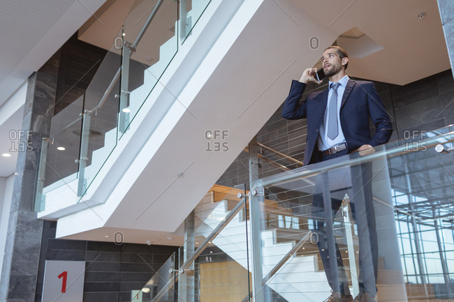 Low angle view of businessman talking on mobile phone near railing in a modern office building