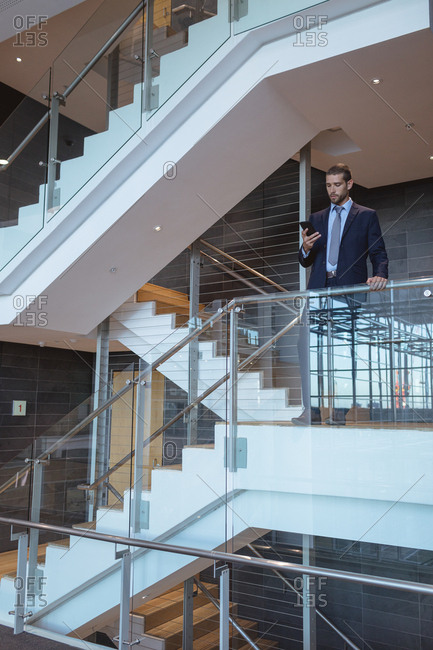 Front view of businessman using mobile phone near railing in a modern office building