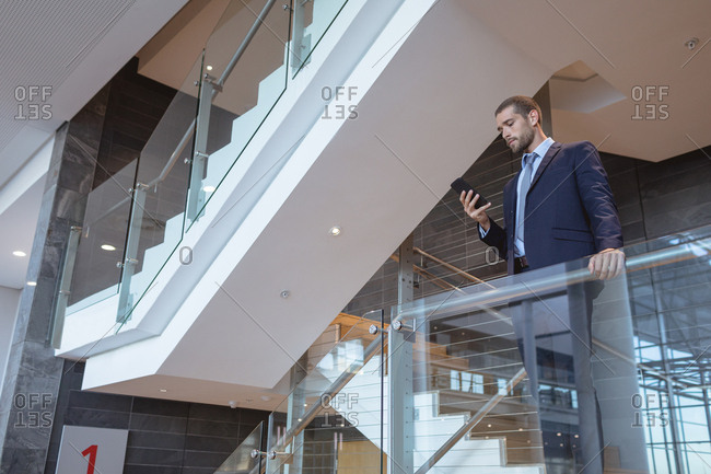 Low angle view of businessman using mobile phone near railing in a modern office building