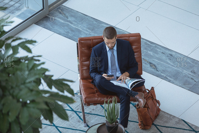 High angle view of businessman using mobile phone in the lobby at modern office