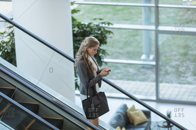 Side view of businesswoman using mobile phone on escalator in a modern office building