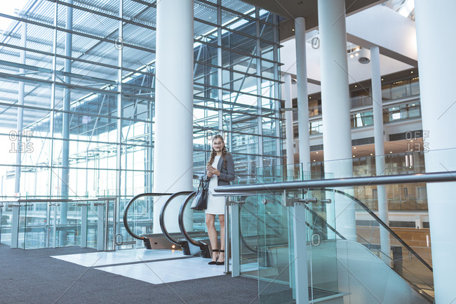 Front view of businesswoman standing near escalator in a modern office building