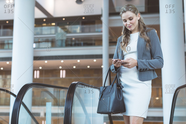 Front view of beautiful businesswoman using mobile phone near escalator in a modern office building
