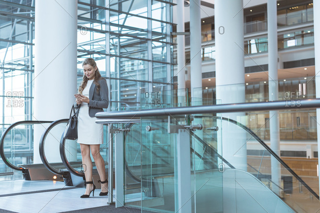 Front view of businesswoman using mobile phone near escalator in a modern office building
