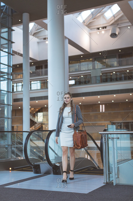 Front view of businesswoman walking near escalator in a modern office building