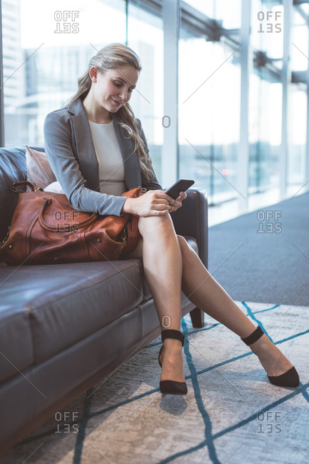 Close-up of businesswoman using mobile phone on sofa in the lobby at modern office