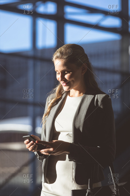 Close-up of businesswoman using mobile phone in lobby at modern office building