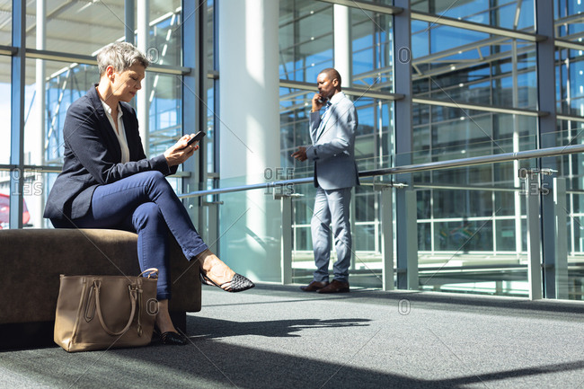 Side view of Caucasian female executive looking at her mobile phone while sitting in a chair in modern office. Behind her,  African american businessman speaking on mobile phone.