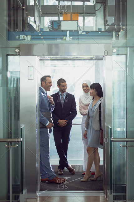 Front view of diverse business people using lift in modern office