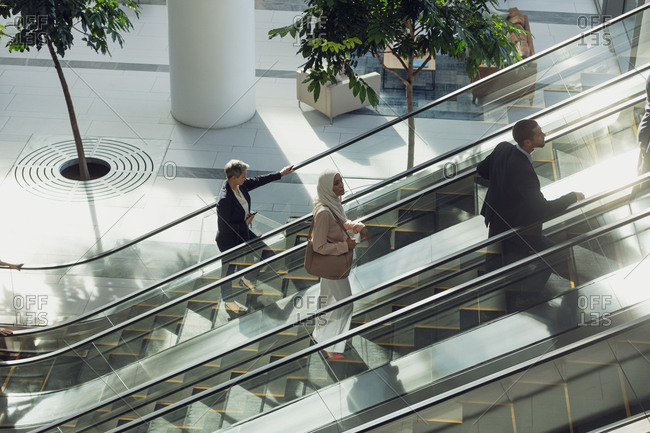 Aerial view of diverse business people using escalators in modern office