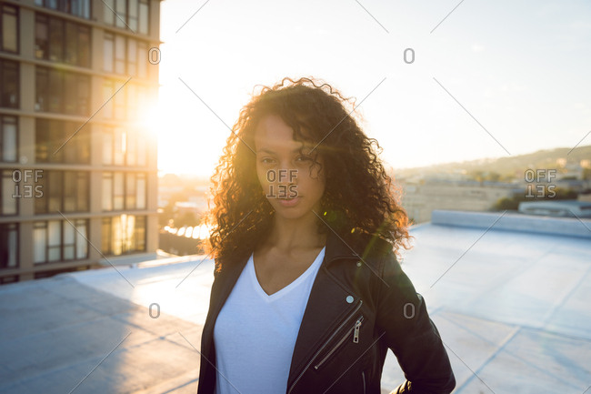 Front view of a young African-American woman wearing a leather jacket looking intently at the camera while standing on a rooftop with a view of a building and the sunset