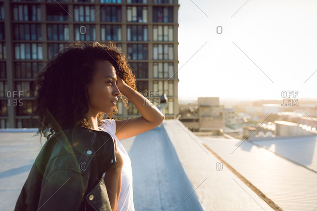 Side view of a young African-American woman with a leather jacket over shoulder looking away from the camera while standing on a rooftop with a view of a building