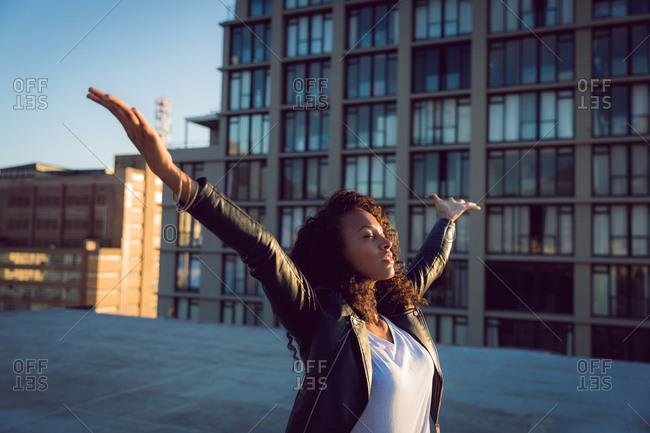 Side view of a young African-American woman wearing a leather jacket looking away from the camera with arms raised while standing on a rooftop with a view of a building