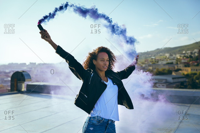 Front view of a young African-American woman wearing a leather jacket holding a smoke maker producing a blue smoke on a rooftop with sunlight