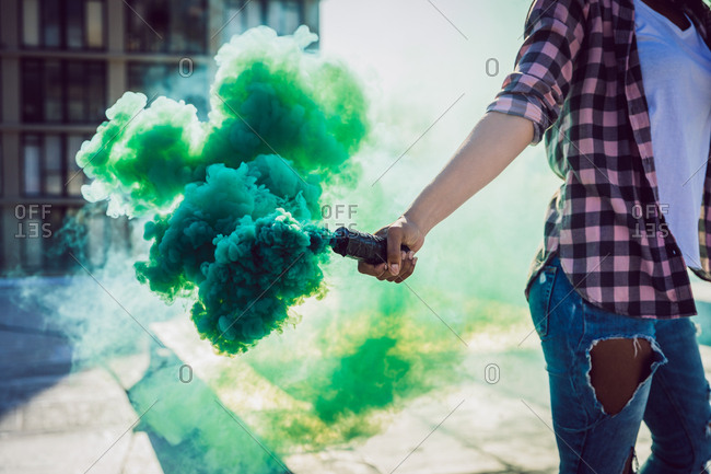 Mid section of a woman wearing a plaid jacket holding a smoke maker producing green smoke on a rooftop with a view of a building and sunlight