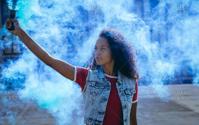 Front view of a young African-American woman wearing a denim vest holding a smoke maker producing blue smoke