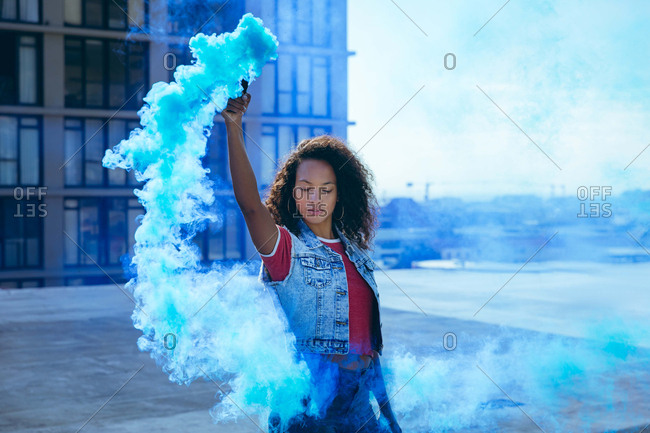 Front view of a young African-American woman wearing a denim vest holding a smoke maker producing blue  smoke on a rooftop with a view of a building and sunlight