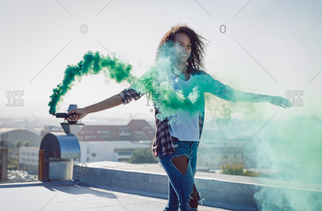 Front view of a young African-American woman wearing a denim vest holding a smoke maker producing green smoke on a rooftop with sunlight