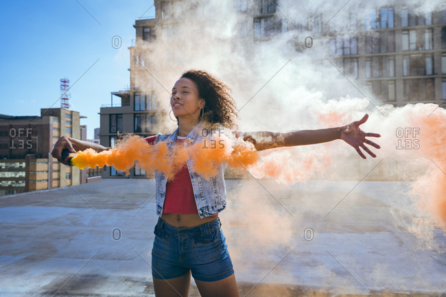 Front view of a young African-American woman wearing a denim vest with arms stretched out and holding a smoke maker producing orange smoke  on a rooftop with a view of a building and sunlight