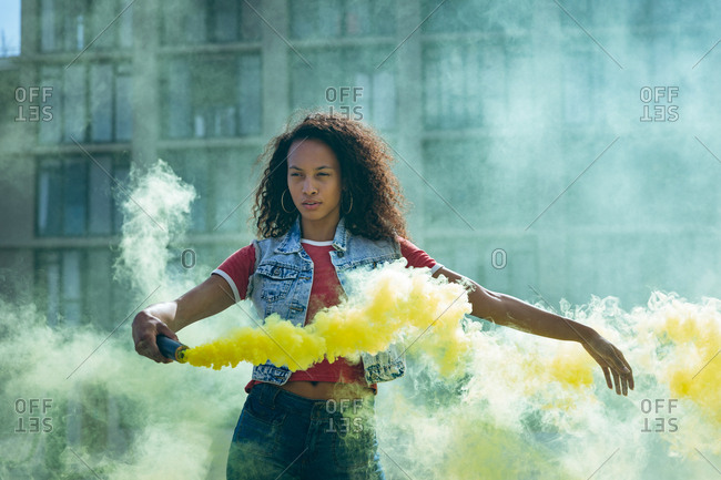 Front view of a young African-American woman wearing a denim vest holding a smoke maker producing yellow smoke  on a rooftop with a view of a building and sunlight