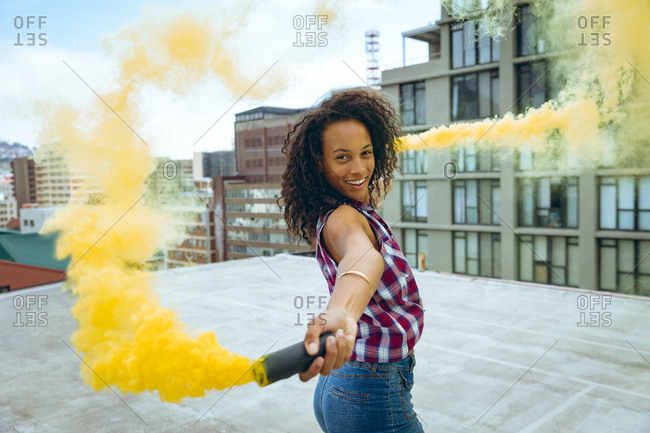Side view of a young African-American woman wearing a plaid top smiling while holding a smoke maker producing yellow smoke on a rooftop with a view of buildings