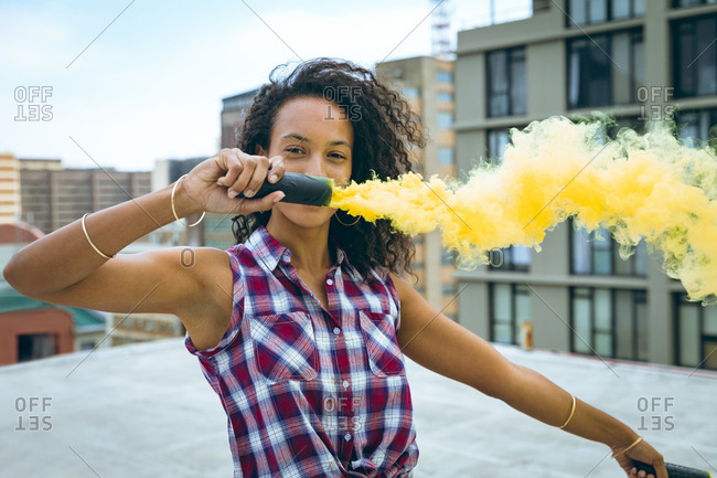 Front view of a young African-American woman wearing a plaid top holding a smoke maker producing yellow smoke on a rooftop with a view of buildings