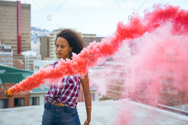 Front view of a young African-American woman wearing a plaid top while holding a smoke maker producing red smoke on a rooftop with a view of buildings