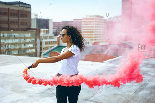 Side view of a young African-American woman wearing a white shirt and eyeglass holding a smoke maker producing red smoke on a rooftop with a view of buildings