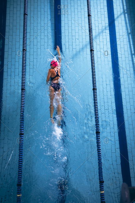 High angle view of a Caucasian woman wearing a pink swimming cap and goggles doing a freestyle stroke in a swimming pool